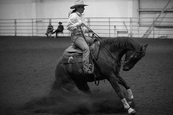 A reining horse is pulled to a sliding stop and hyperflexed by a cowgirl.