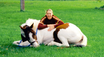 Paint gelding laying down, while his rider sits behind him smiling.